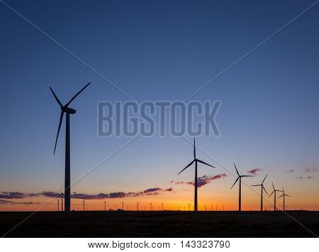 A row of wind turbines as the sun rises.