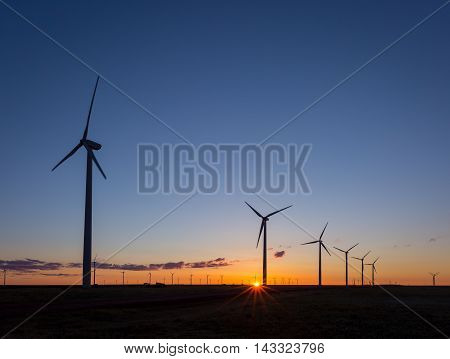 The sun peaks over the horizon as a row of wind turbines spin in the foreground.