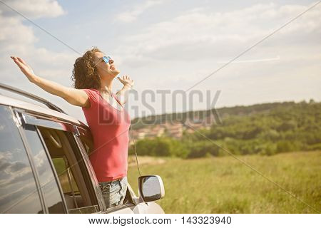 Absolute freedom. Happy brunette girl enjoying freedom on roadtrip vacation and raising arms