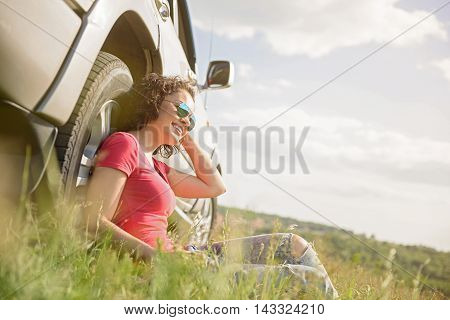 Roadtrip relaxation. Shot of young woman sitting on grass next to her car while on roadtrip