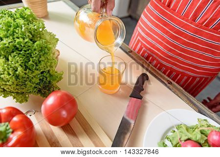 Close up of male hand pouring orange juice into glass in kitchen. Man is standing near table with healthy food and holding jar
