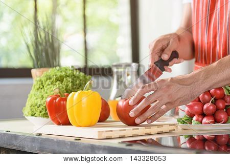 Close up of male arms cutting tomato on board. Man is standing near table in kitchen