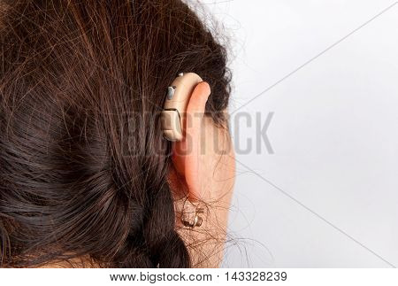 A Woman wearing a brown hearing aid