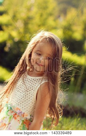 beautiful baby girl summer evening having fun in the sunlight the wind ruffles your hair. The coy smile of the model