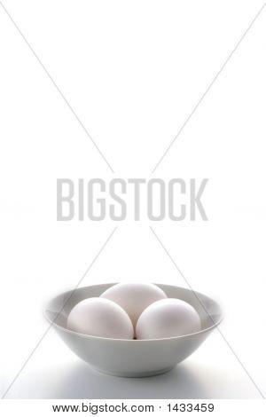 Three White Eggs In A White Bowl