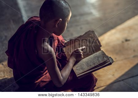 Young Buddhist novice monk reading and study in monastery Myanmar