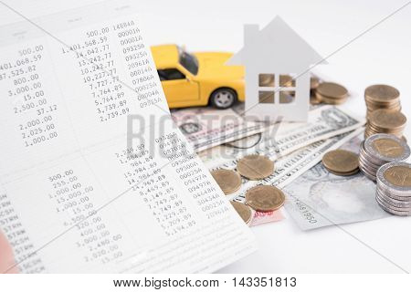 money pile coin with account book and paper home car family on white background business car and home finance insurance concept