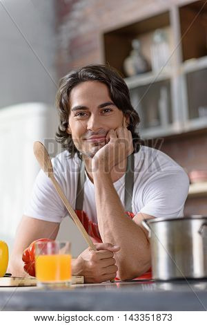 I like cooking. Happy young man is standing in kitchen with relaxation. He is leaning on table and holding wooden spoon. Man is smiling