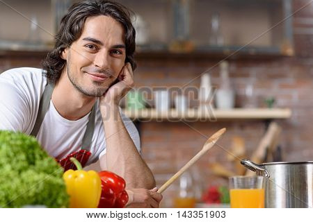 Relaxed young man is in expectation of self-made dish. He is standing in kitchen and leaning on table. Guy is smiling with happiness