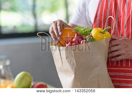 Close up of male hands taking fresh orange from shopping packet. Man is standing in kitchen