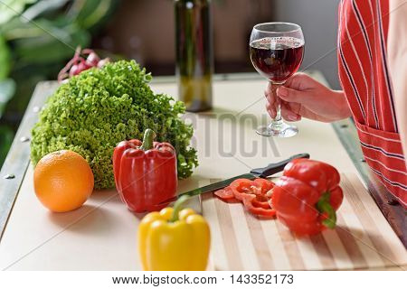 Close up of female hand holding glass of red wine. Woman is standing near table with vegetables in kitchen