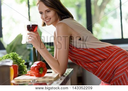 Happy young housewife is relaxing while cooking romantic dinner. She is drinking wine and smiling. Woman is leaning on table and dreaming
