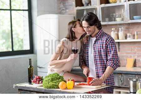 Young man is preparing romantic dinner for his wife. He is cutting vegetable and smiling. Woman is kissing him with love. She is sitting on table in kitchen and holding wineglass