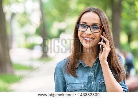 Carefree girl is using phone for communication and smiling. She is standing in park and looking at camera with happiness