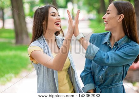 We have done it. Joyful two women are giving high five. They are standing in park and laughing. Friends are looking at each other with happiness