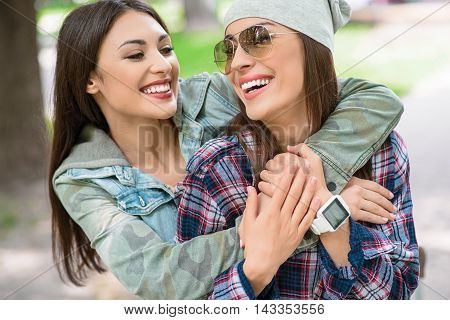 Joyful lesbian couple is embracing and smiling. Women are standing in park