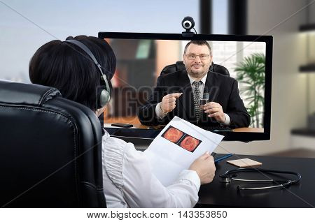 Virtual female doctor sits face to face with patient in black suit in monitor. Physician in headset carefully exams his virtual colonoscopy or CT colonography result before coming to a conclusion. Middle-aged handsome businessman is ready to take a pill