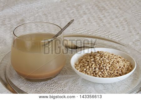 Barley water in a glass with a dish of pearl barley.