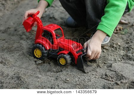 Children play in the fresh air. Boy playing with a red plastic car a digger in sand.