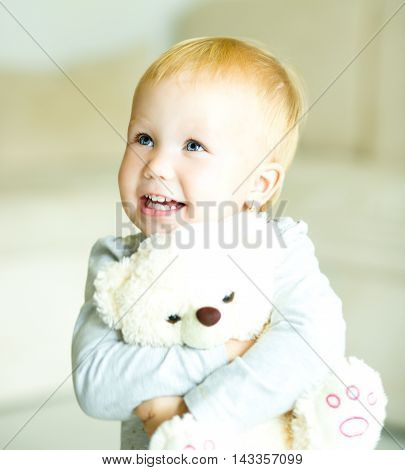 Little cute girl is playing her teddy bear