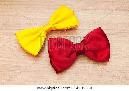 Two bow ties on the wooden background