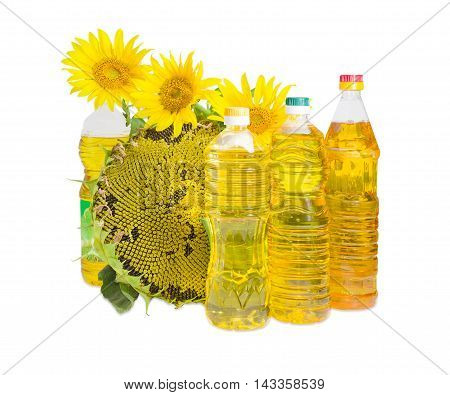 Several plastic bottles of sunflower oil of different variety ripening sunflower head with seeds and flowers of sunflower on a light background
