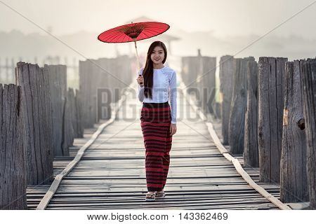 Burmese woman holding traditional red umbrella and walking on U Bein Bridge