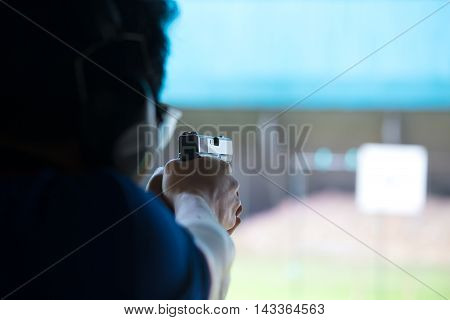 a man aim and shoot pistol to white paper target by two hand in academy shooting range focus on gun