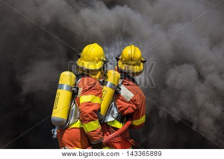 two firefighter in fire fighting suit spraying high pressure water to fire and black smoke