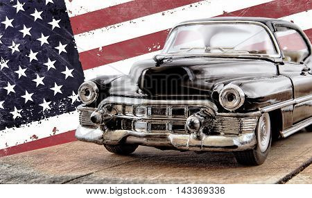 The toy car against the American flag. The traditional American car 1960 years. On a background the shabby American flag. The car is located on the scratched wooden board. Vmd in front and sideways. The car is made of metal with the chromeplated details.
