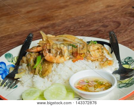 Spicy fried shrimp with basil leaves on the wood table.