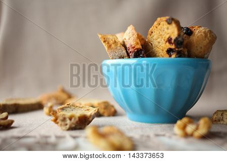 Italian biscotti cookies with nuts in the blue bowl on the table with grey linen tablecloth