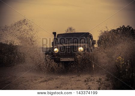 Novgorod oblast, Russia , 03 August, 2015 , Jeep Wrangler on a rural road in the Novgorod region, the Jeep Wrangler is a compact four wheel drive off road and sport utility vehicle