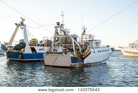 Two trawlers moored at the port in Italy