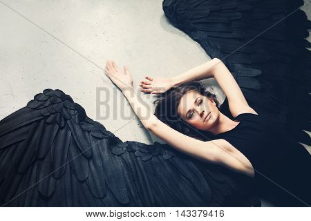 Sensuality Woman Black Angel Relaxing on gray