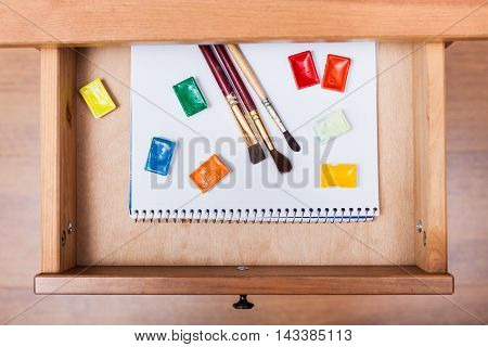 Paint Brushes And Water Paints On Album In Drawer