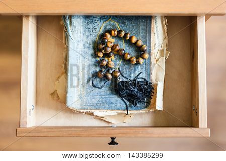 Rosary On Shabby Religious Book In Open Drawe