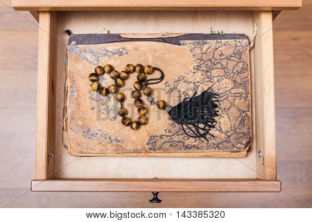 Rosary On Ansient Book In Open Drawer