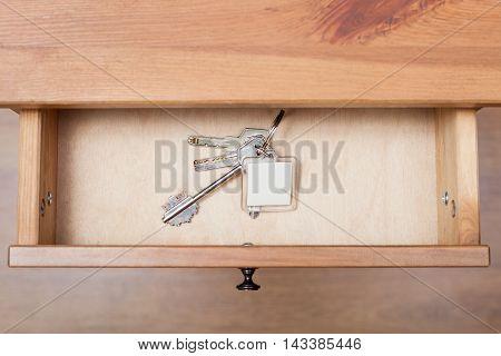 Bunch Of Door Keys With Keychain In Open Drawer