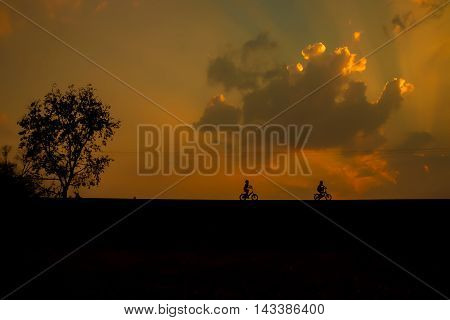 Silhouette cyclist with reflection at sunset .