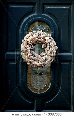 Modern christmas wreath with cones on classic door