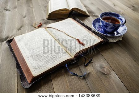 Peaceful Christian religious scene of two open Bibles with cup of tea on wooden table background. Bibles are non trademark version.