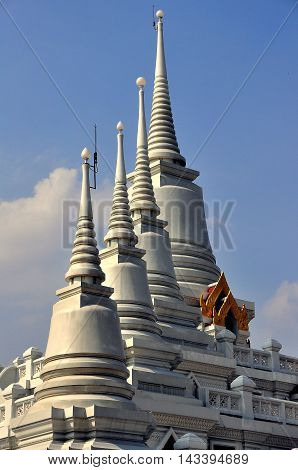Samut Prakan Thailand - January 15 2013: Four glistening white Chedis with ringed spires atop the great temple at Wat Asok
