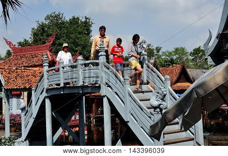 Samut Prakan Thailand - January 15 2013: Family crossing the quaint Floating Market bridge at Ancient Siam Heritage Park