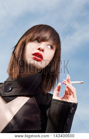 the beautiful young elegant girl with a cigarette