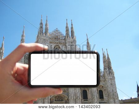 Hand holding a cell phone with a blank screen in front of Duomo di Milano cathedral in Milan, Italy. Travel tourism concept background.