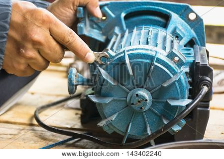 Electric motor  and man working equipment repair on wooden floor background.Background craftsman or equipment.Zoom in