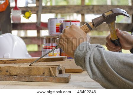 Carpenter using  chisel and hammer in his hand with plank.Close up and stillife.