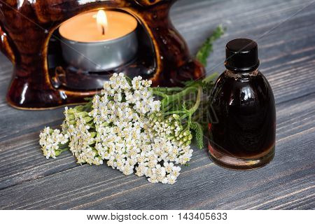 Essential yarrow oil and flower candle on dark wooden background.