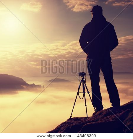 Photographer on cliff. Nature photographer takes photos with mirror camera on peak of rock. Dreamy fogy landscape spring orange pink misty sunrise in a beautiful valley below.